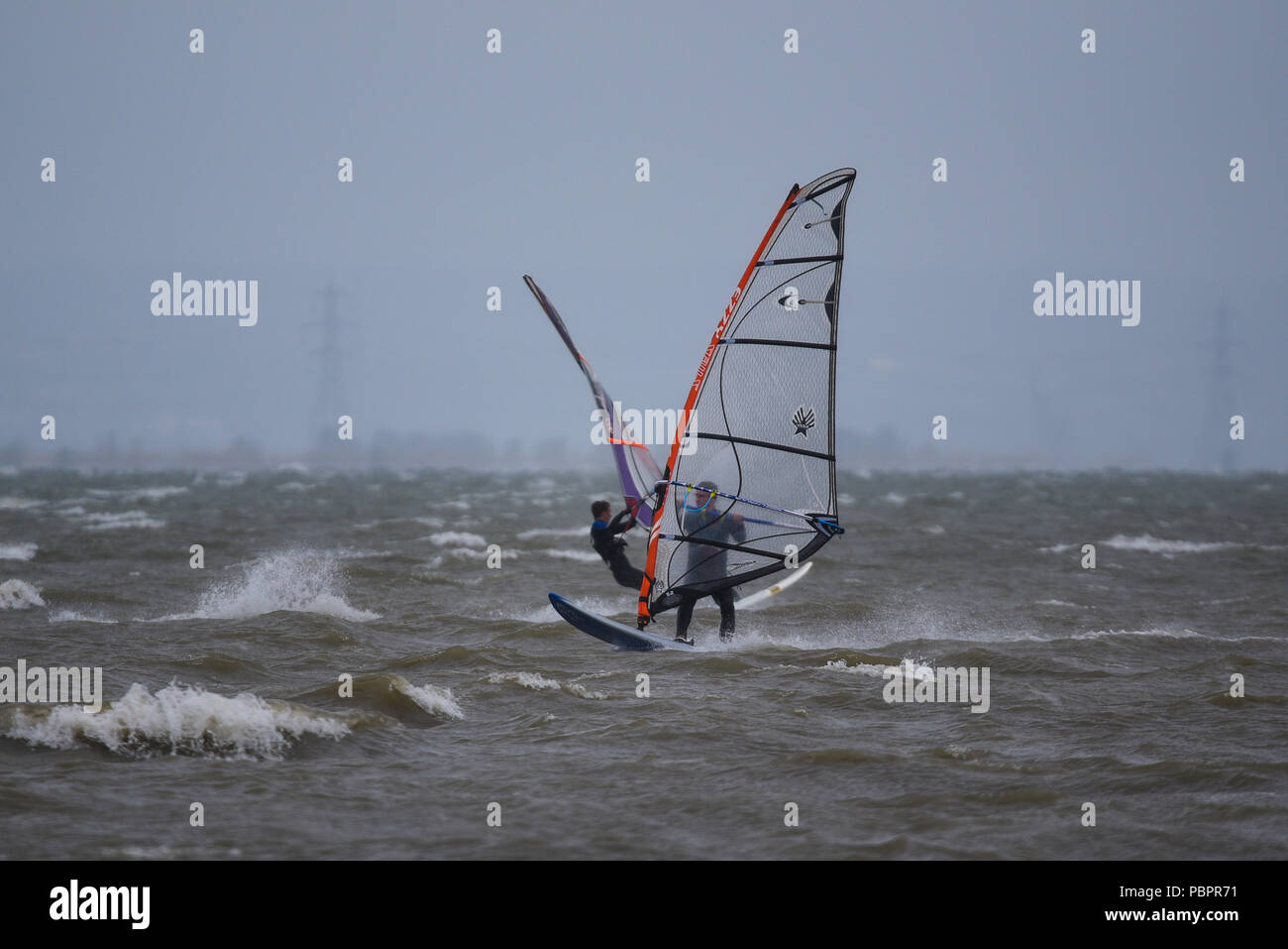 Southend-on-Sea, Essex, UK. Strong winds and rain have hit the south east of the UK. Windsurfers took to the Thames Estuary off Southend Stock Photo
