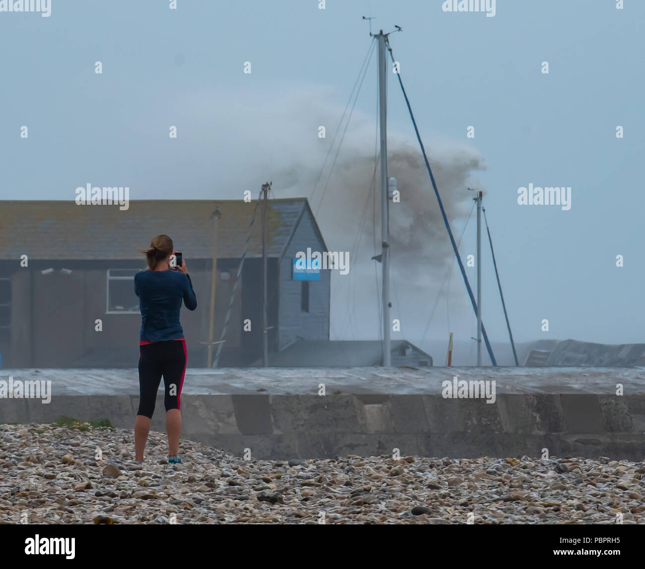 Lyme Regis, Dorset, UK. 29th July 2018.  UK Weather: Storm waves crash into seafront at Lyme Regis. A storm hits the seafront and the historic Cobb Harbour at the seaside resort of Lyme Regis bringing a temporary lull to the record breaking summer heatwave. A young woman takes a snap from the safety of the beach. Credit: Celia McMahon/Alamy Live News - Stock Image