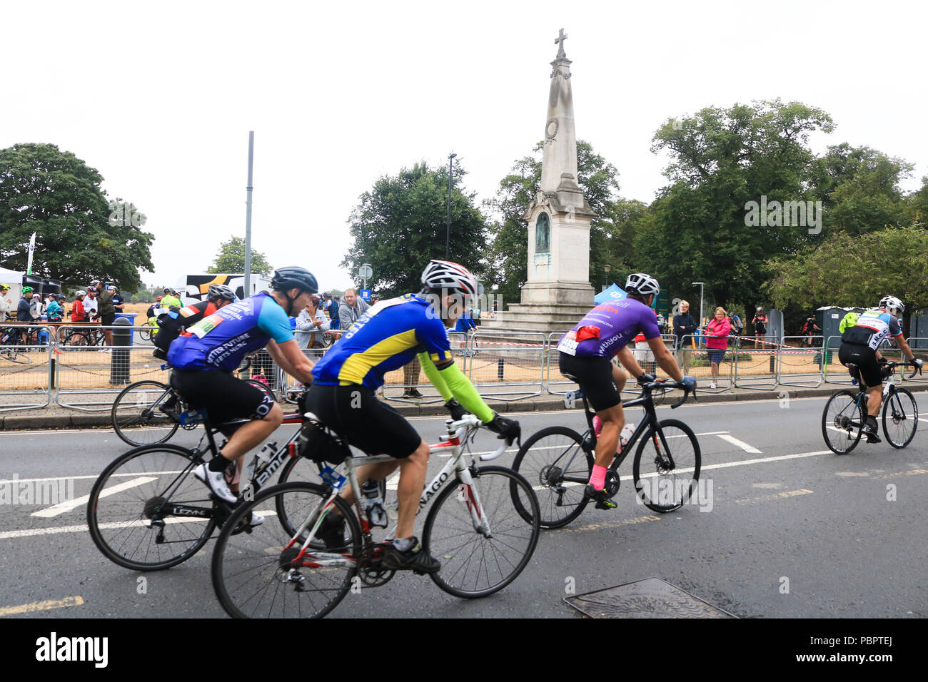 Thousands of Cyclists ride through Wimbledon village in the Prudential  London Surrey 100 classic event on a overcast rainy day . 50db57805