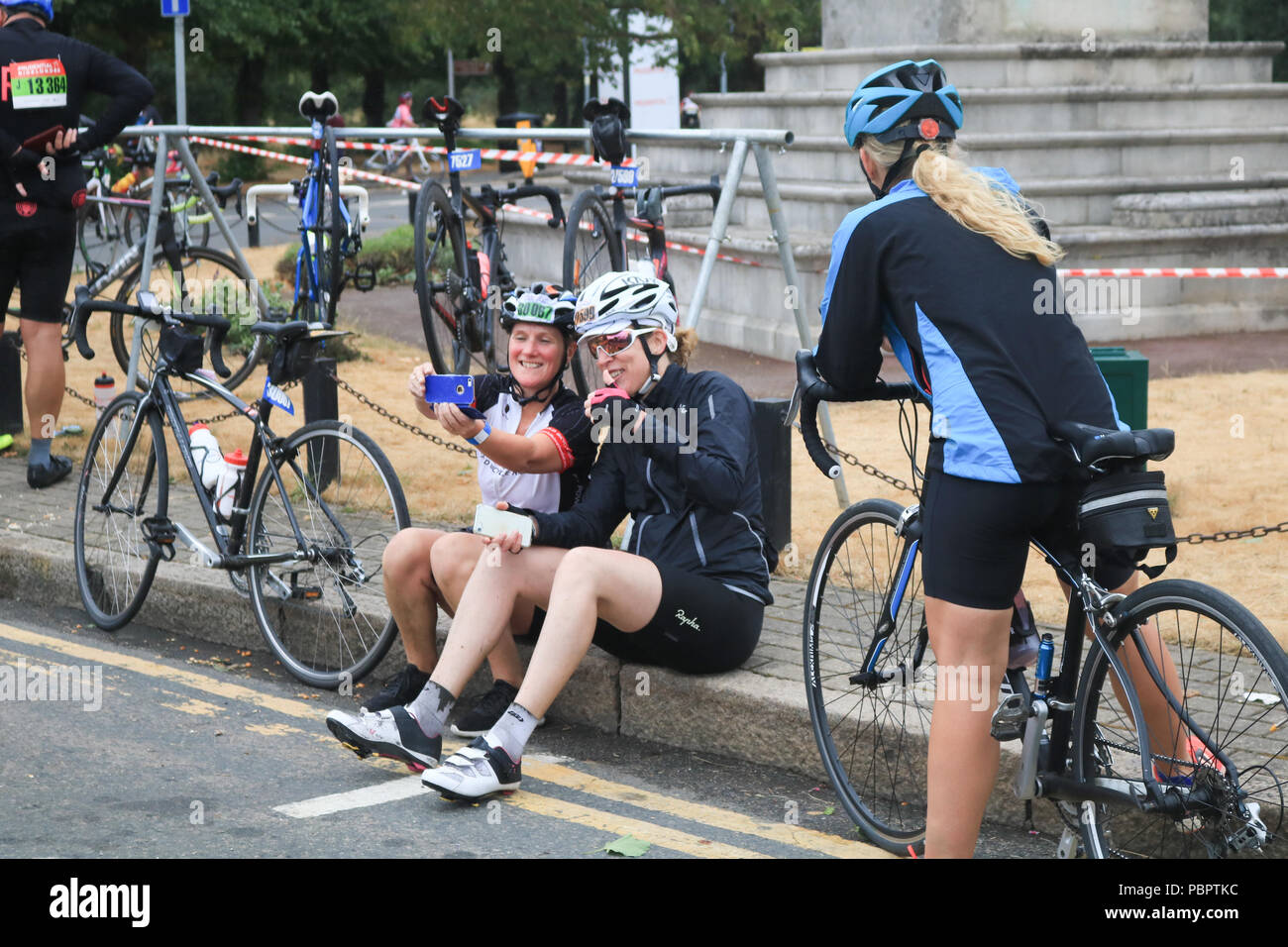 Cyclists make a pit stop as they ride through Wimbledon village in the  Prudential London Surrey 100 classic event on a overcast rainy day . 1f8b02cc3