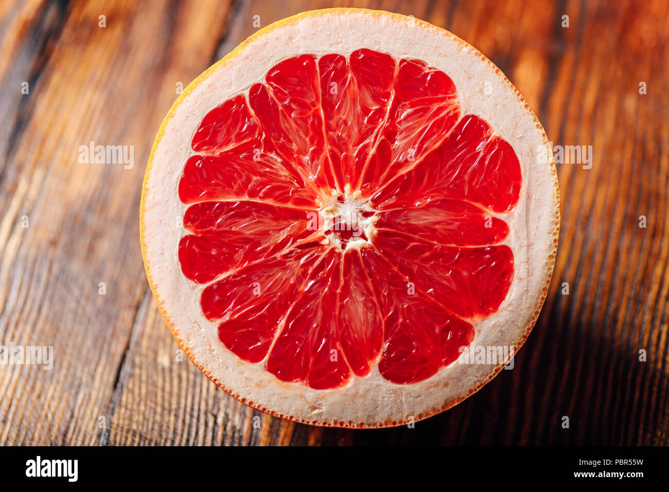 Half of Ripe and Juicy Grapefruit on Wooden Table. - Stock Image