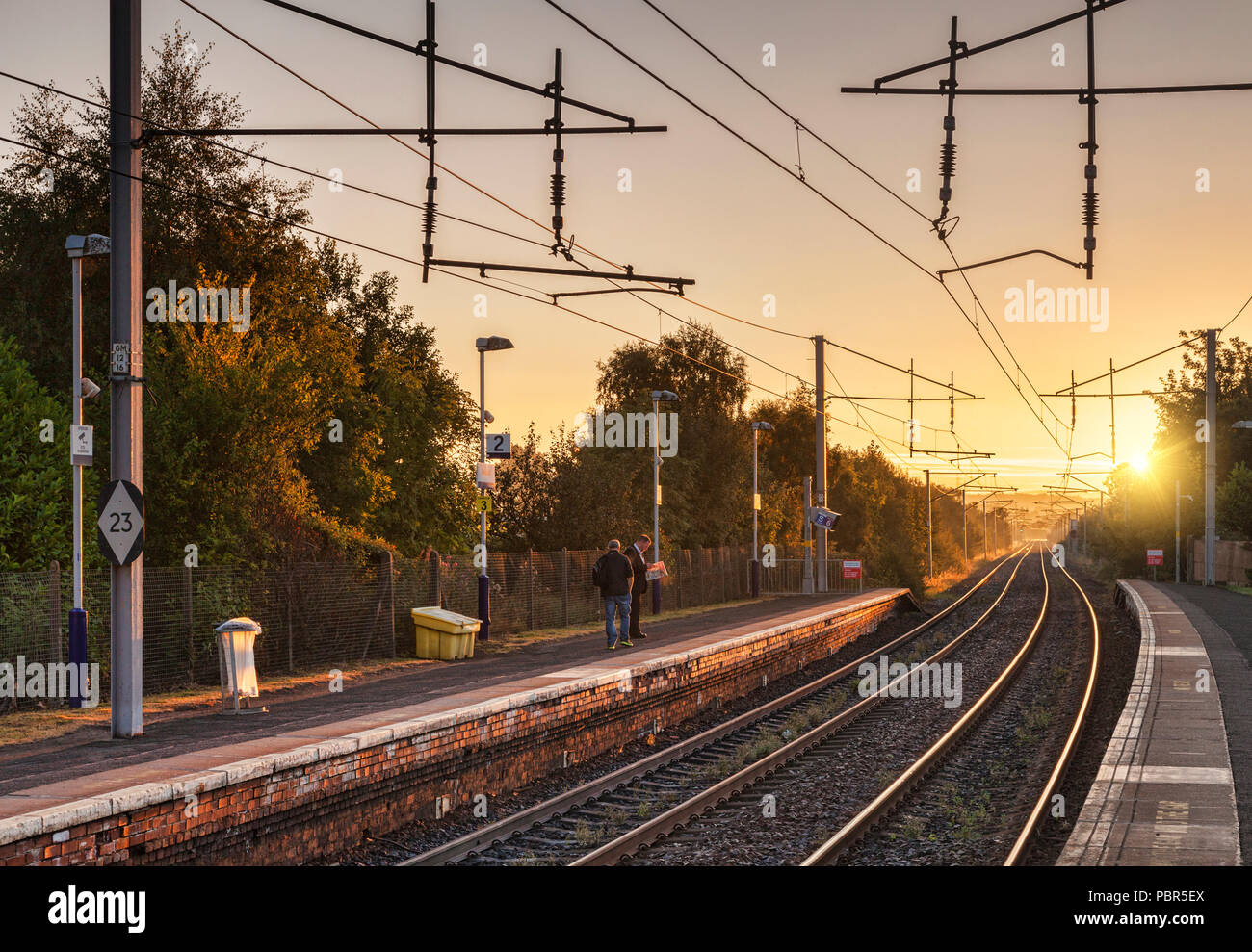 Waiting on a railway platform for a train in the early morning as the sun comes up. Bellshill Station, Glasgow, Scotland. - Stock Image