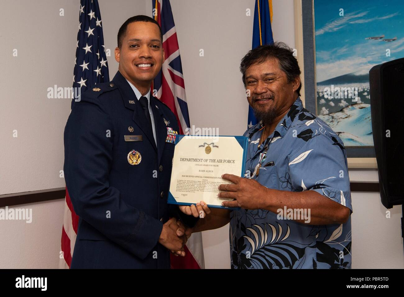 Lt. Col. Wade McGrew, 21st Space Operations Squadron commander, presents the Air Force Civilian Award for Valor to Robin Albios, Detachment 3, 21st SOPS heating, ventilation and air conditioning specialist, at the Kaena Point Satellite Tracking Station, Hawaii, July 23, 2018. Two years ago, Albios provided medical aid to a state of Hawaii volunteer field crew member who suffered from smoke inhalation during a fire at the Kuaokala Game Management Area. (U.S. Air Force photo by Tech. Sgt. Heather Redman) - Stock Image