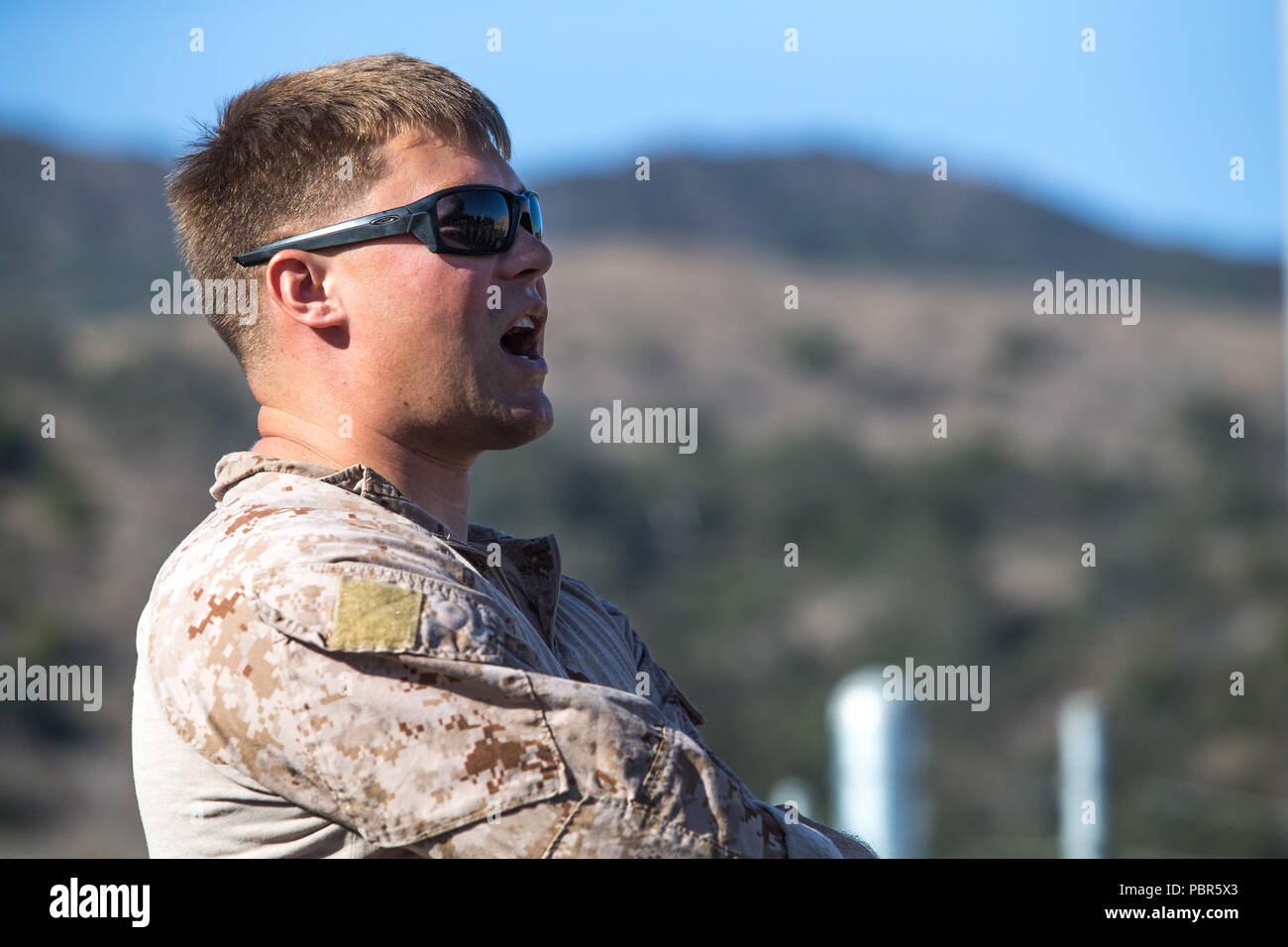 U.S. Marine Corps Staff Sgt. Daniel Ragan, unit leader, Light Armored Reconnaissance Training Company, Advanced Infantry Training Battalion, gives instructions to class 5-18 during a training exercise at Marine Corps Base Camp Pendleton, California, July 24, 2018. Ragan conducted a gear check and taught class 5-18 the importance of using hand signals while guiding Light Armored Vehicles. (U.S. Marine Corps Photo by Pfc. Stephen Beard) - Stock Image