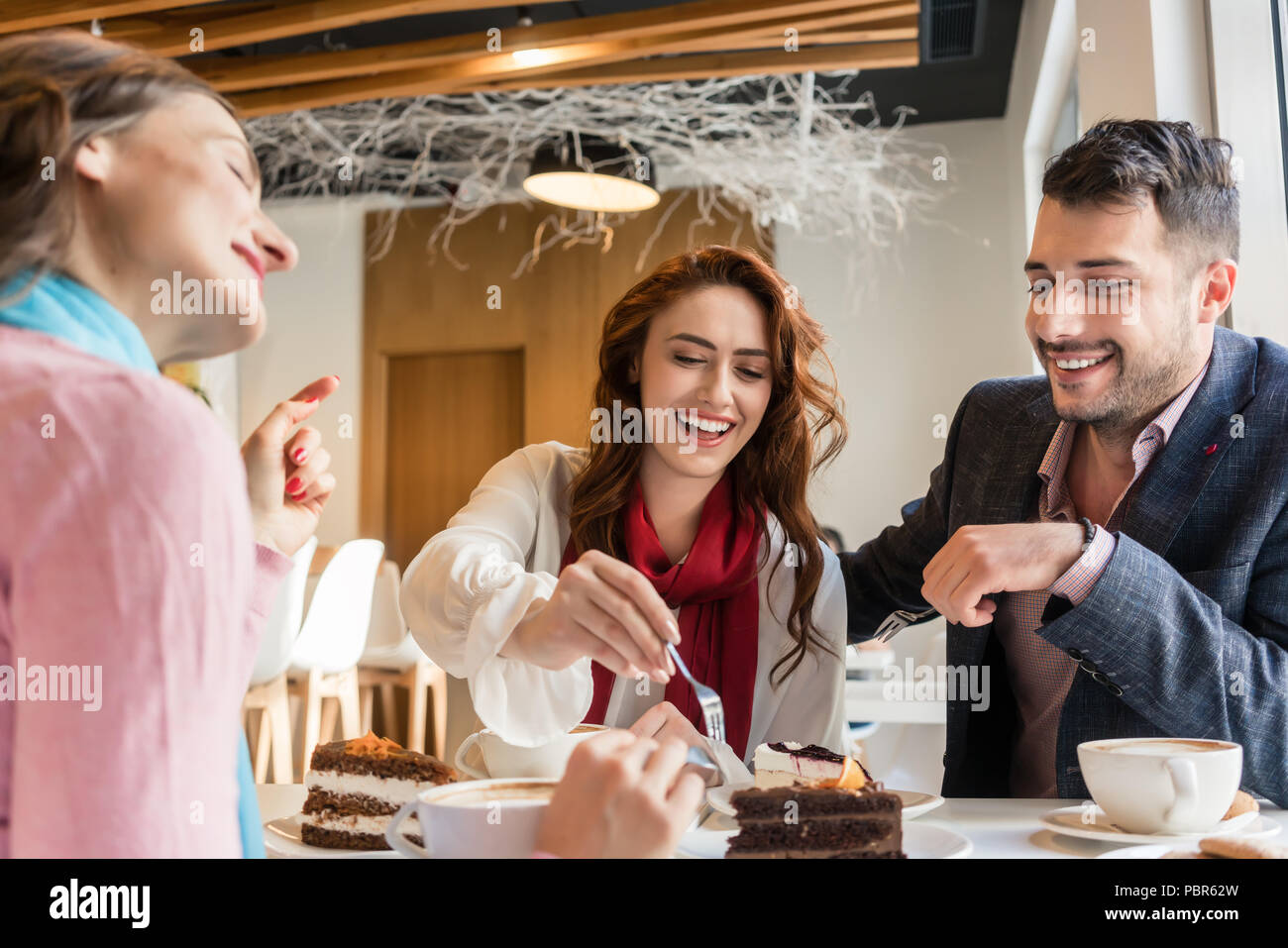 Three friends smiling while eating delicious cakes in their cheat day - Stock Image