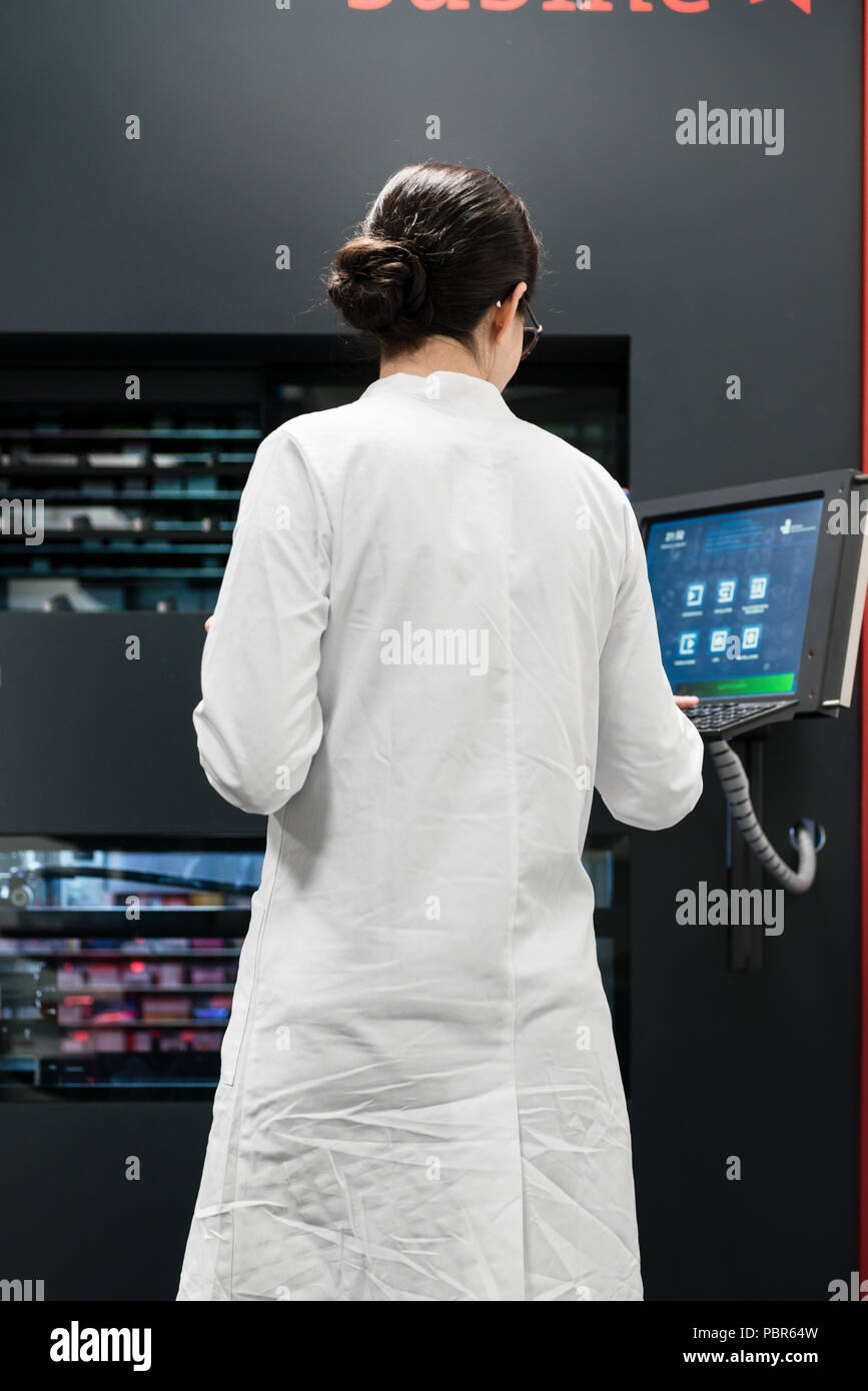 pharmacist using a computer while managing the drug stock in pharmacy - Stock Image
