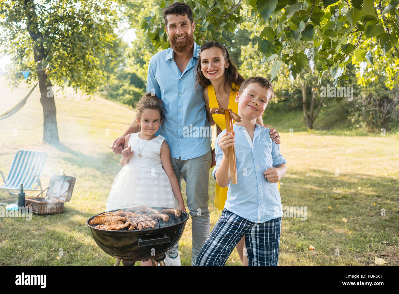 Portrait of happy family with two children standing outdoors - Stock Image