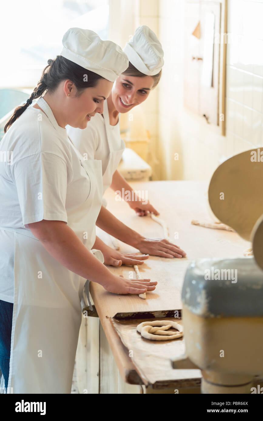 Baker women working in bakehouse of bakery - Stock Image