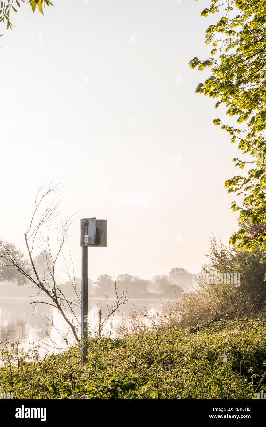 Dawn riverside scene. Trees and one kilometre distance marker on riverbank on a misty Spring morning on the River Trent, Nottinghamshire, England, UK - Stock Image