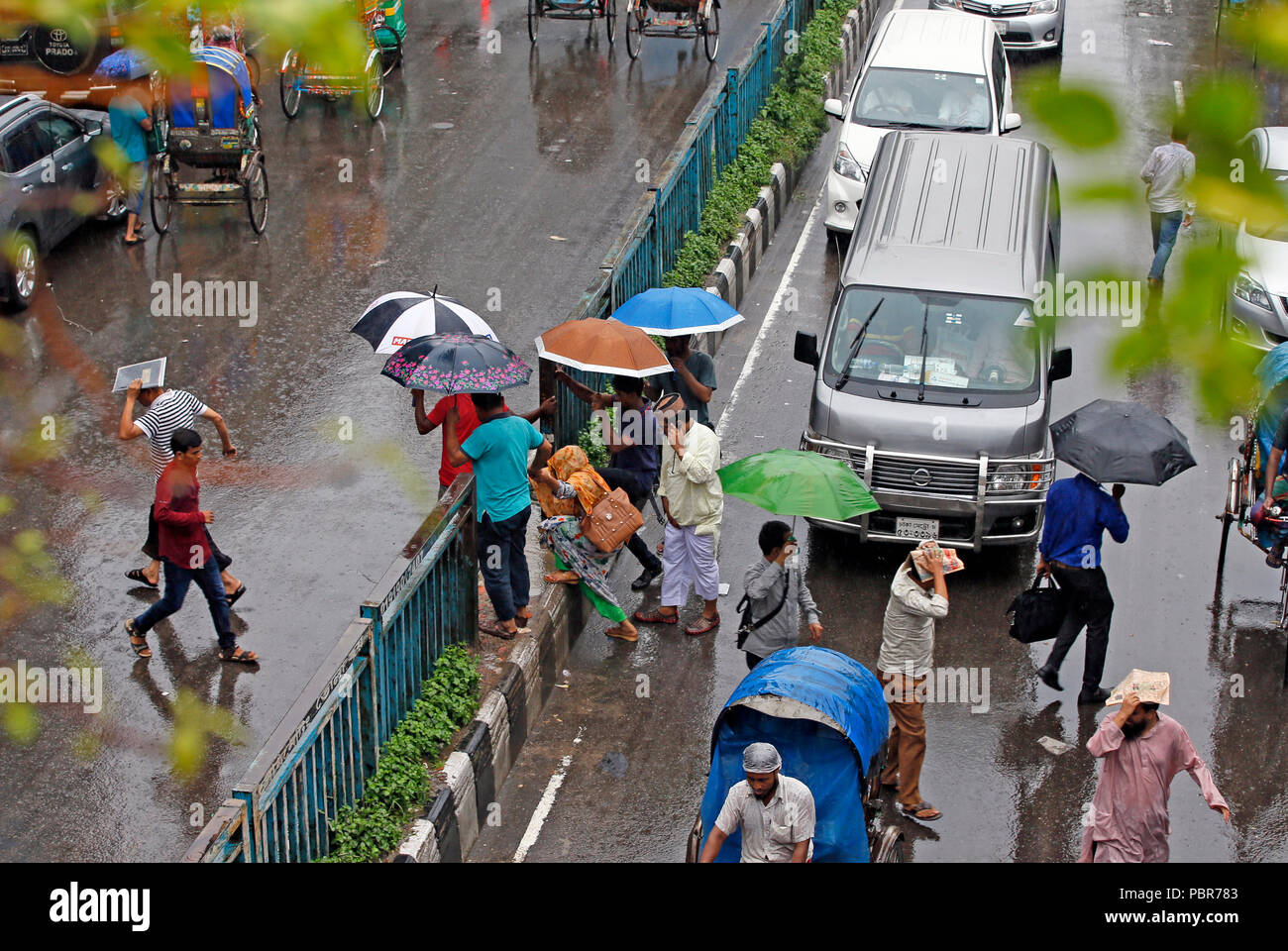 City dwellers caught in heavy shower at Capital's Purana Paltan area near National Baitul Mukarram Mosque, Dhaka, Bangladesh. July 24, 2018 - Stock Image