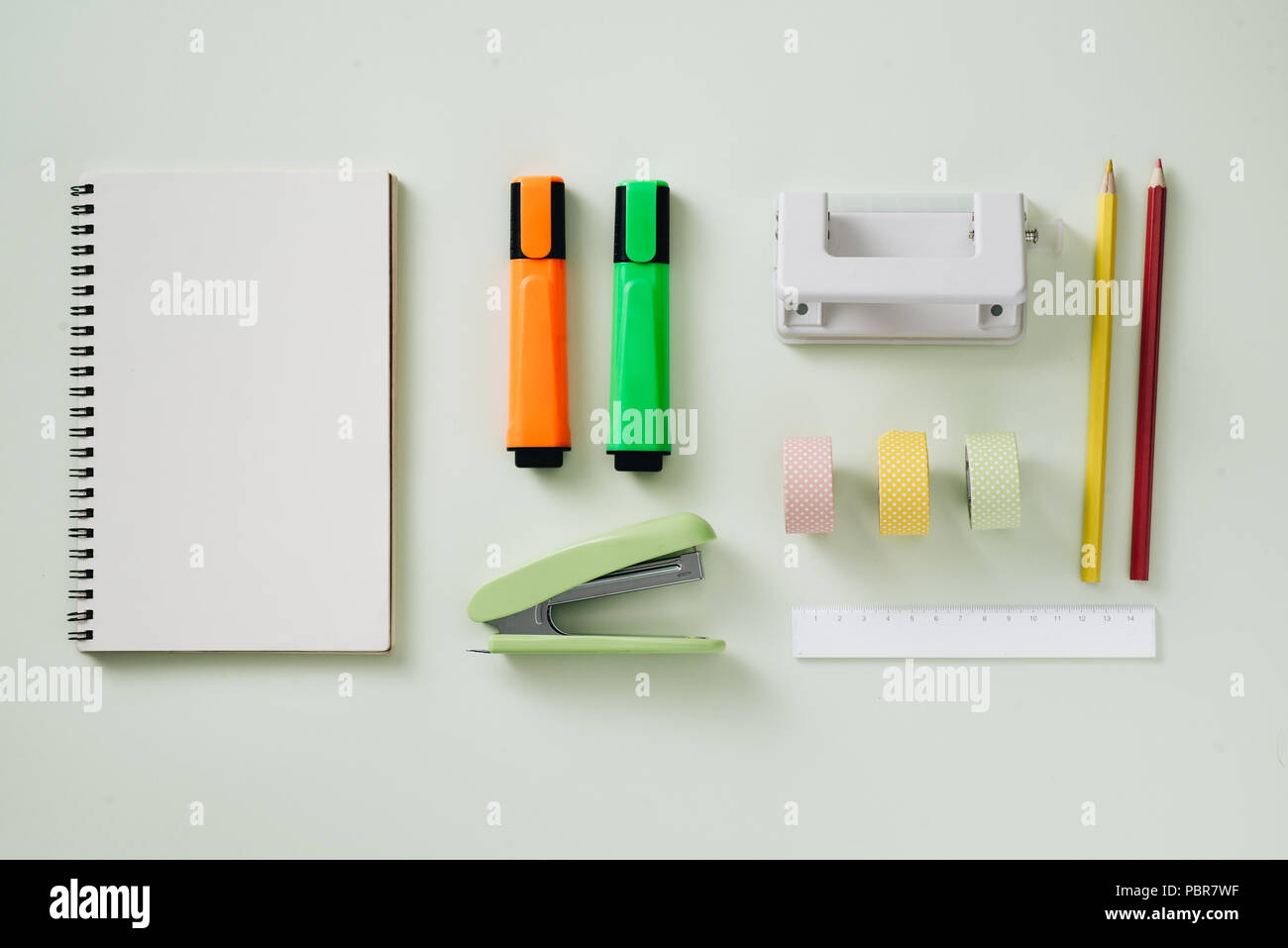 Paper tape roll, paper clips, and notepads laying on a wooden table, School supplies, Office supplies, Back to school Stock Photo