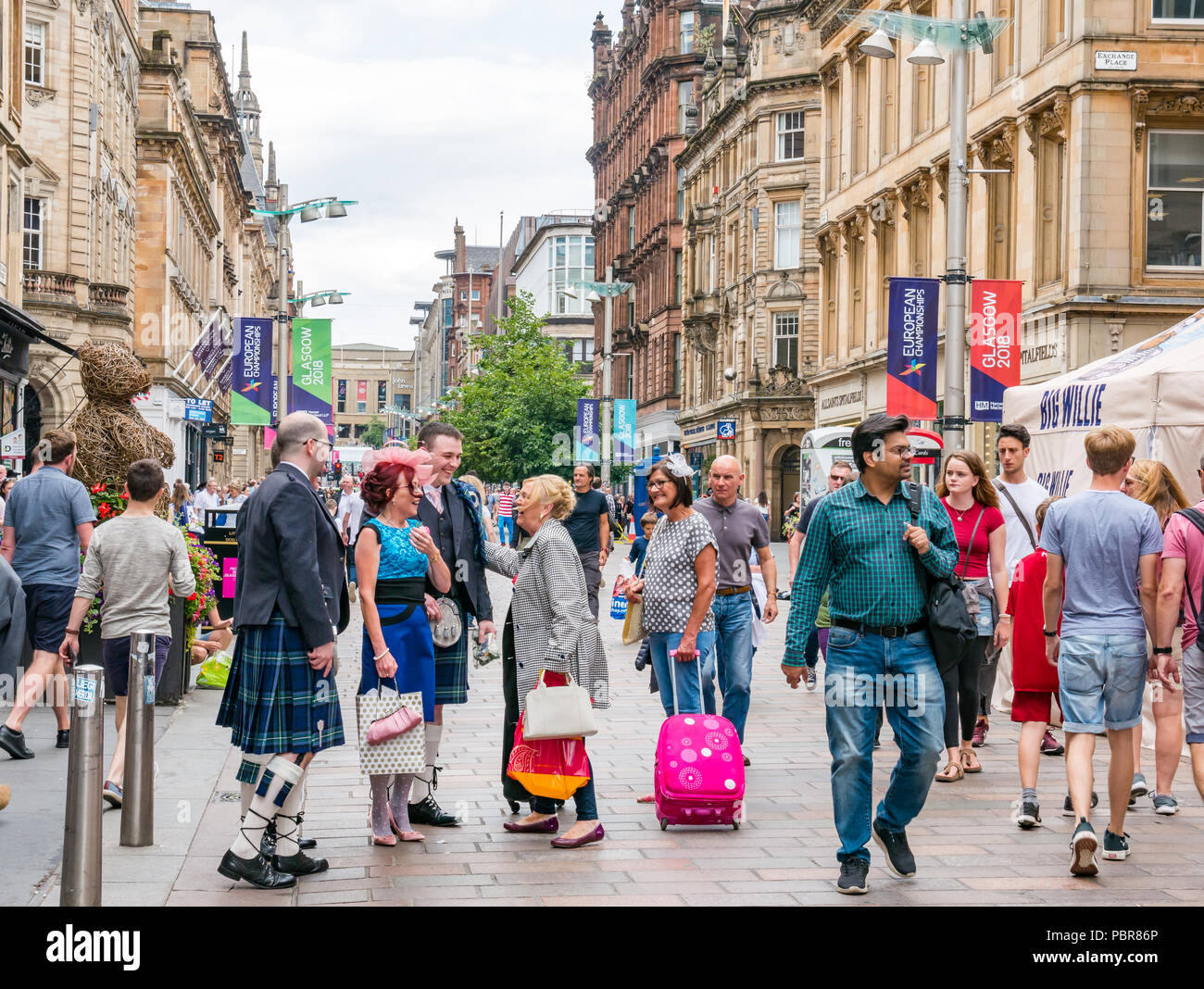 People Dressed For A Wedding With Men In Kilts Stopping To Say Hello