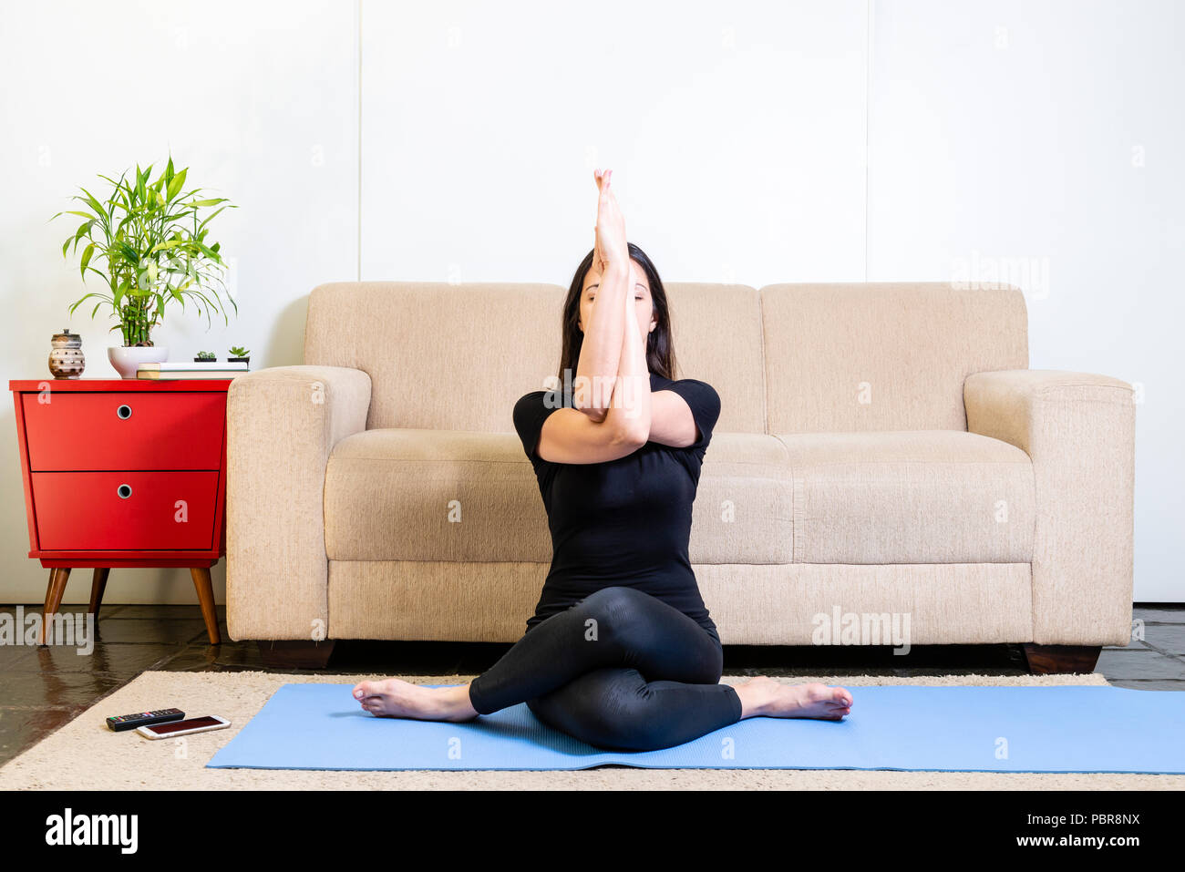 Beautiful caucasian brunette woman in black clothes on blue yogamat doing a variation of the eagle pose - Stock Image