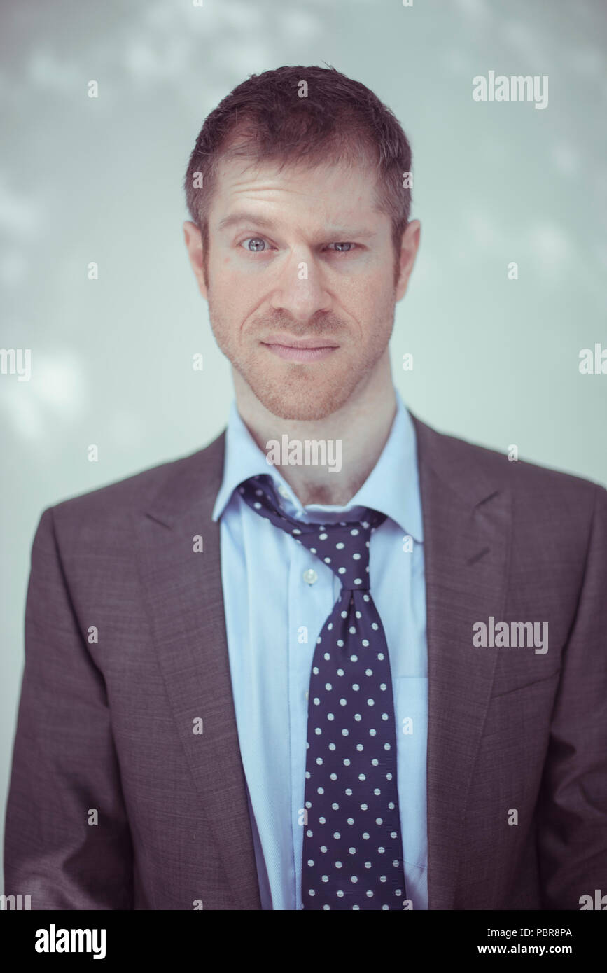 Caucasian male in his 30's wearing a grey suit, raising an eyebrow - Stock Image