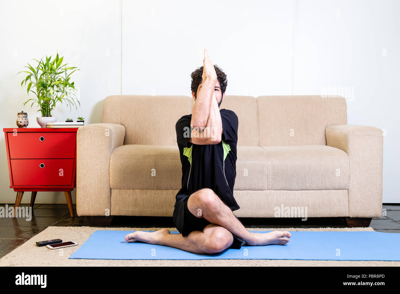 Beautiful caucasian bearded man in black clothes on blue yogamat doing a variation of the eagle pose - Stock Image