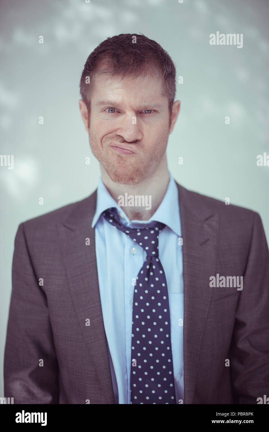 Caucasian male in his 30's wearing a grey suit, working in a tidy desk, with a little laptop, notebooks and a big coffee mug. - Stock Image
