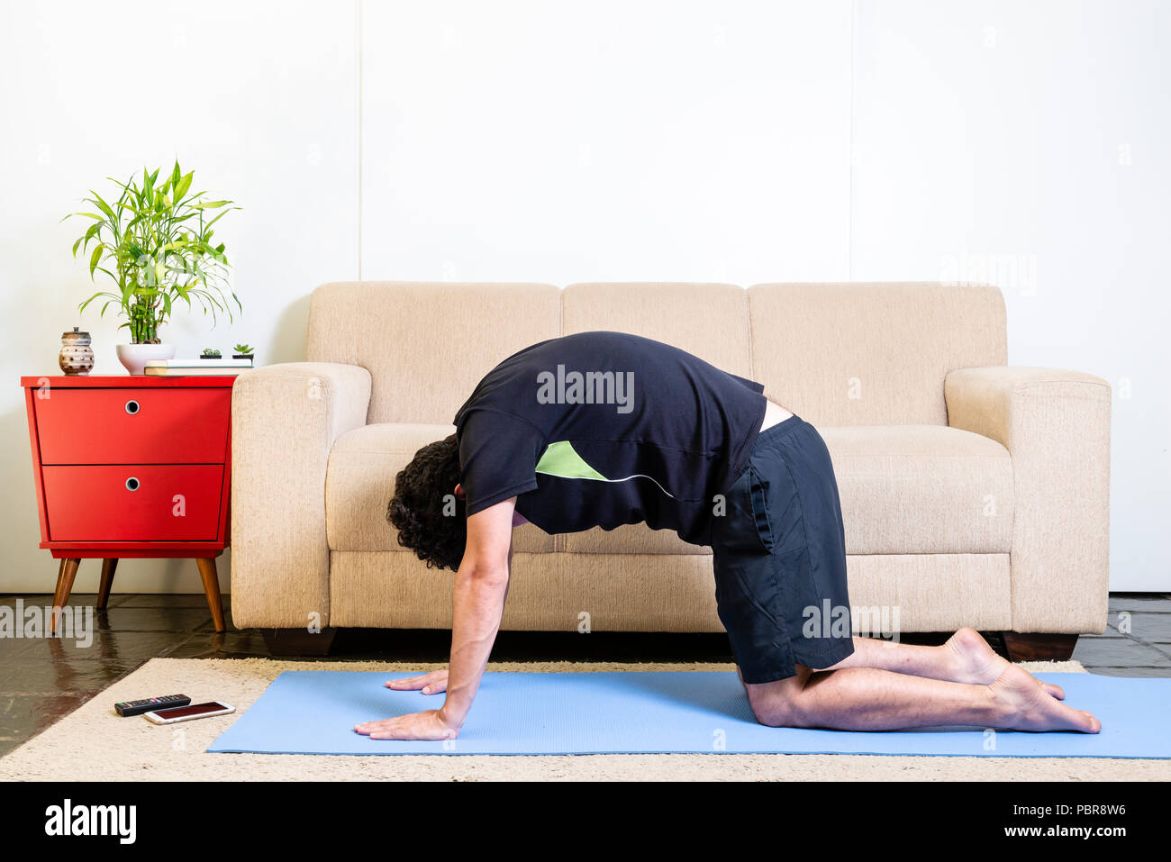 Beautiful caucasian bearded man in black clothes on blue yogamat doing cat pose - Stock Image