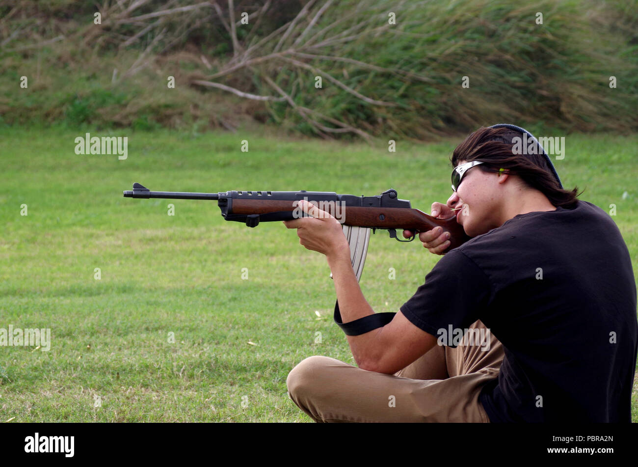 Young man fires a Ruger Mini 14 carbine at a gun range in