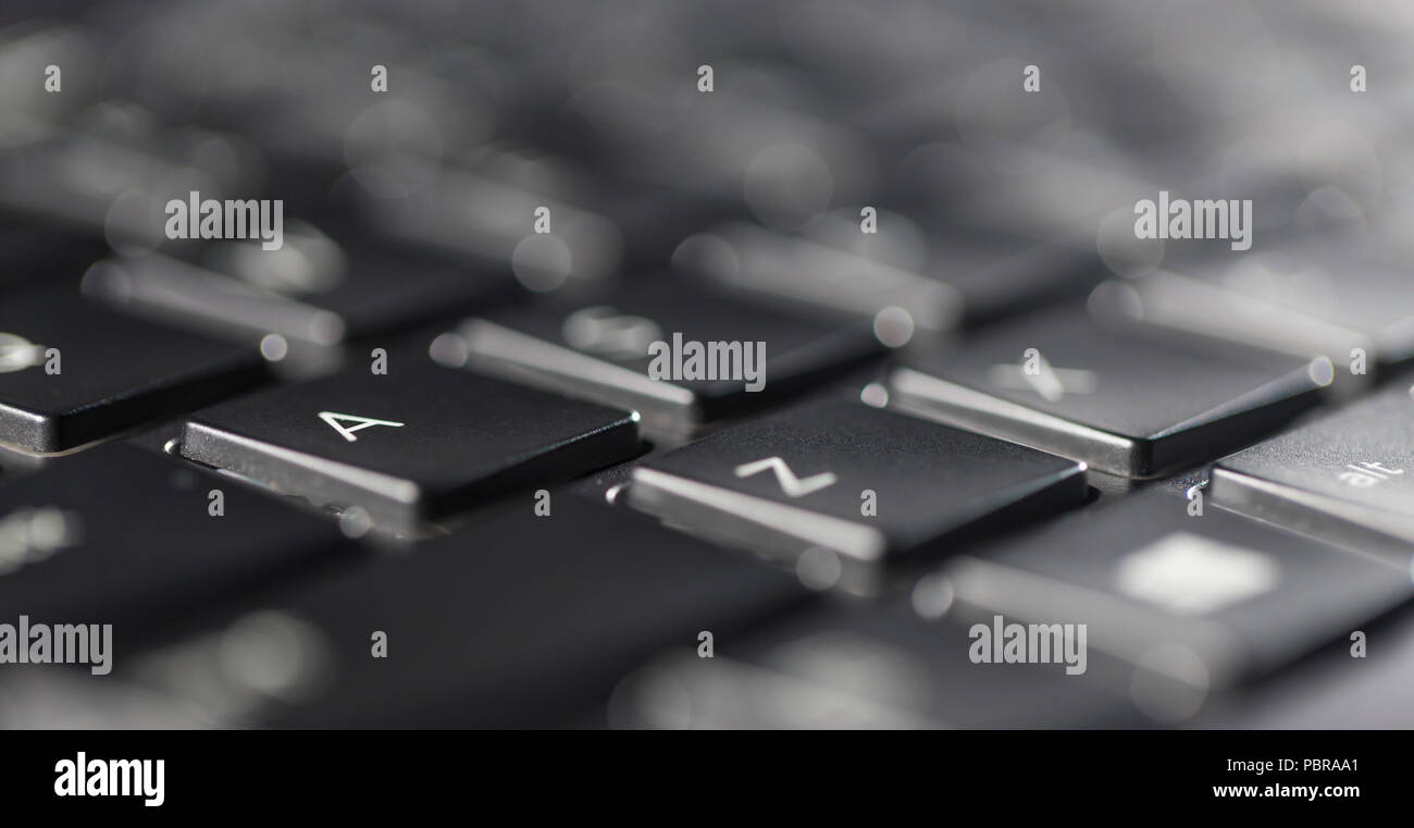 Macro view of black laptop keyboard buttons against back light - Stock Image