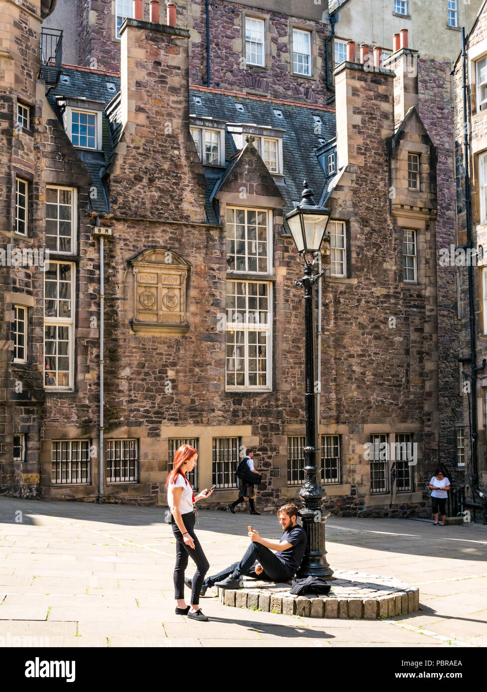 Young couple by old fashioned lamp post relax looking at phones and smoking in Makar's Court outside Writer's Museum, Edinburgh, Scotland, UK - Stock Image
