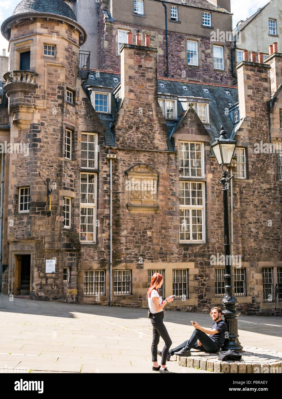 Young couple by old fashioned lamp post relax looking at mobile phones, Makar's Court, Writer's Museum, Edinburgh, Scotland, UK - Stock Image