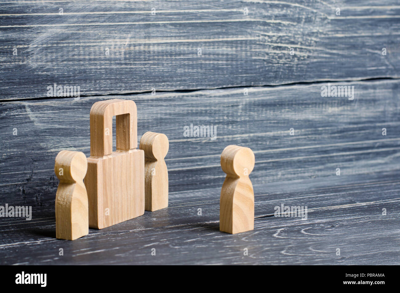 Two people stand near a padlock and keep secrets, information, entrance. Wooden figures of persons carry guards from wicked men, spies. The concept of - Stock Image