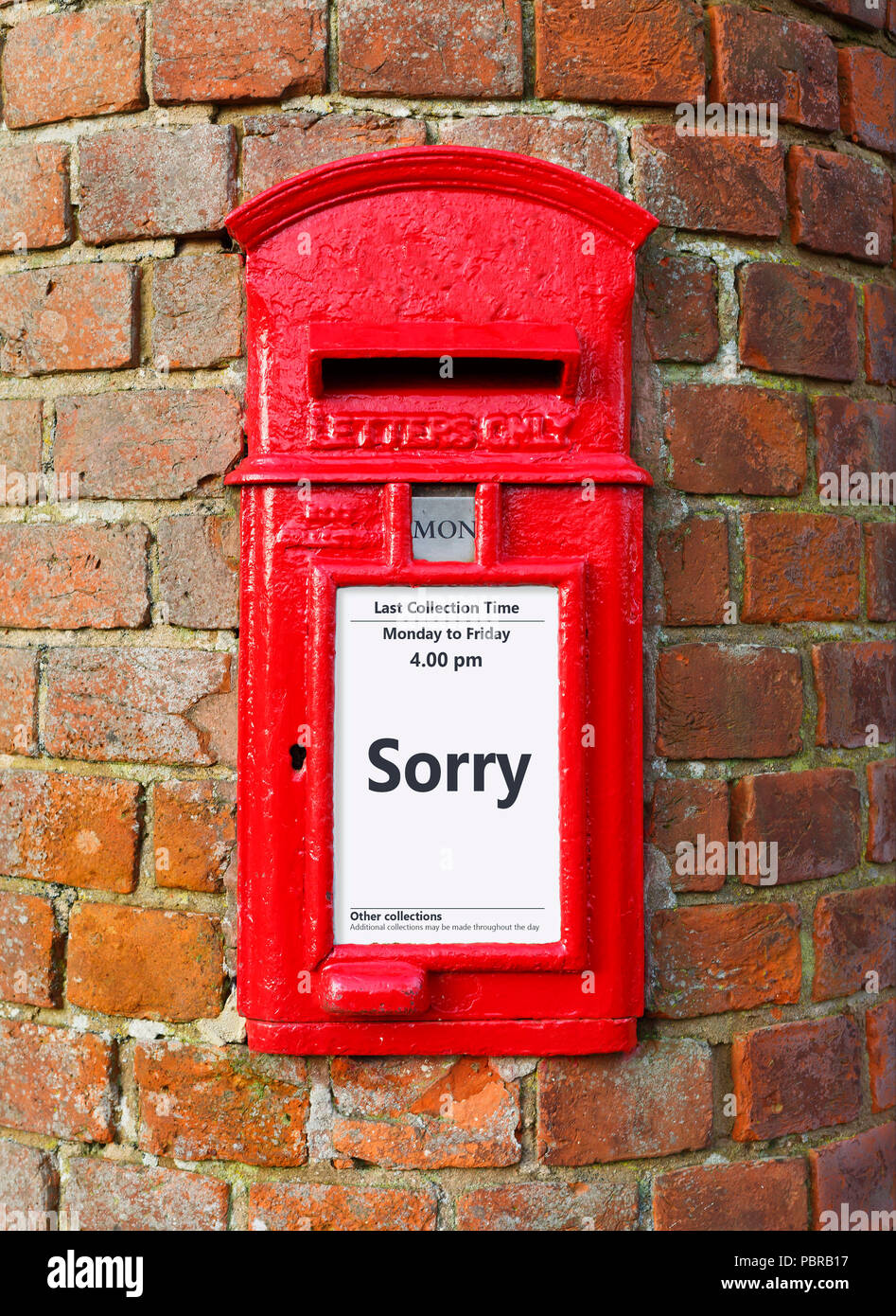British post box with a message that reads Sorry, ideal for a greeting card design - Stock Image