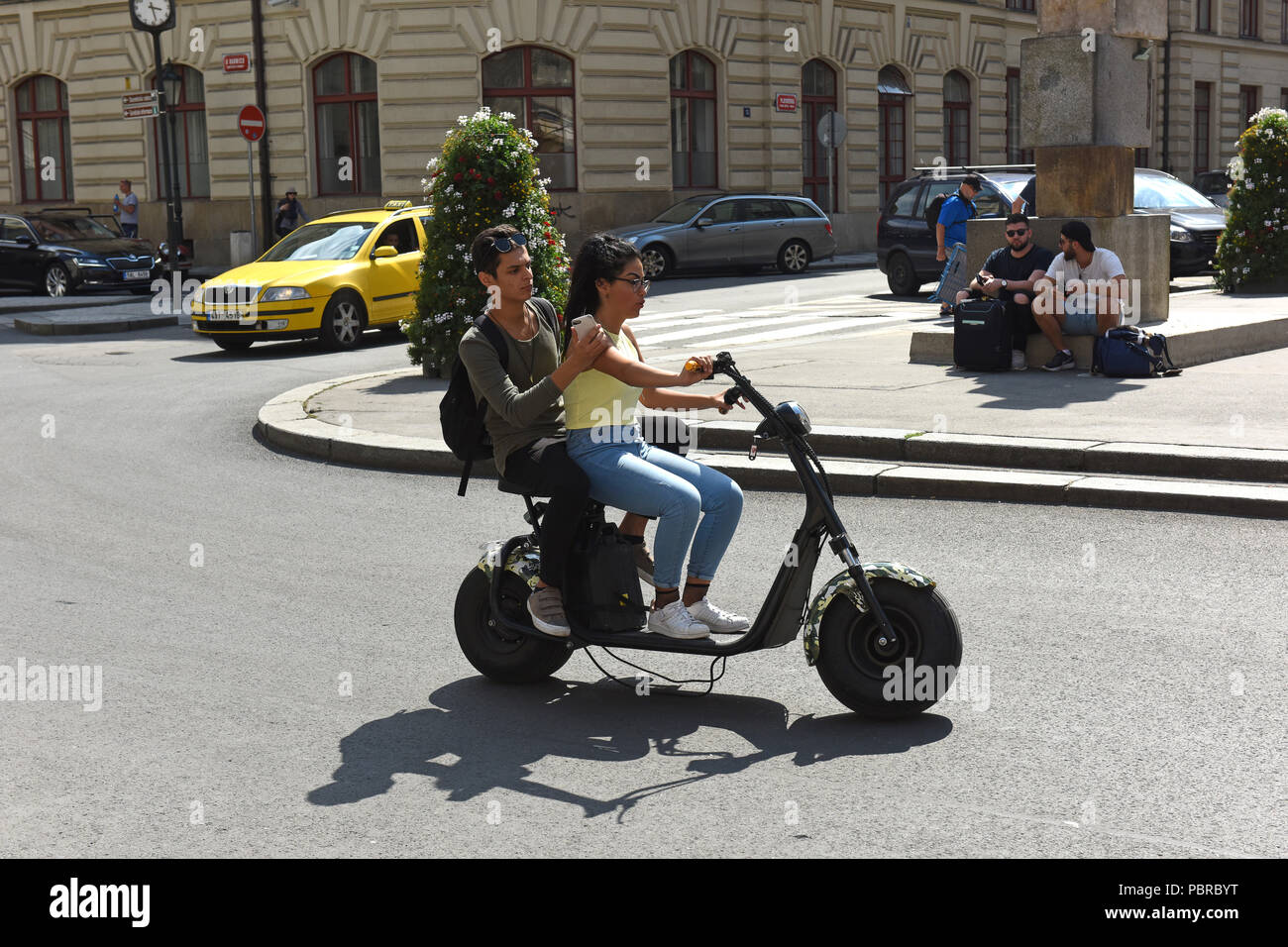 Teenagers teenage youths riding electric scooters in Prague in the Czech Republic - Stock Image