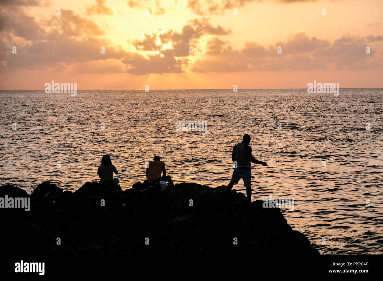 Caymanians people fishing from shore at sunset Cayman Island Stock Photo