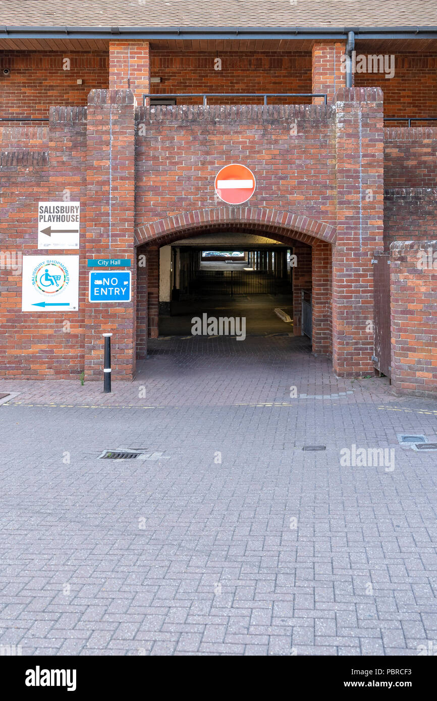 No entry sign on red brick wall above exit from car park - Stock Image