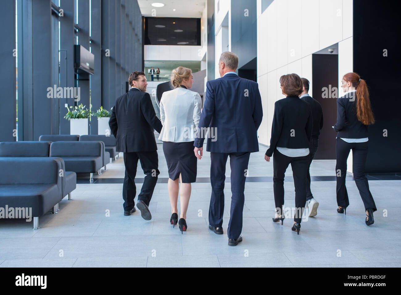 Lively business team walking together in office builging showing teamwork, togetherness and liveliness - Stock Image