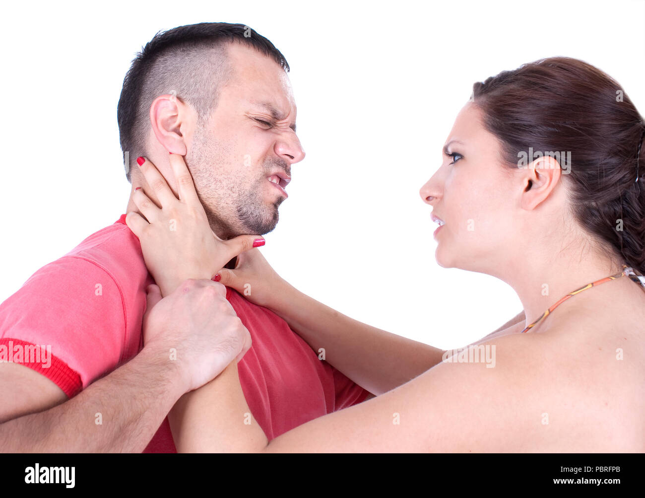 Angry wife from front try to strangle unfaithful husband, studio shot - Stock Image