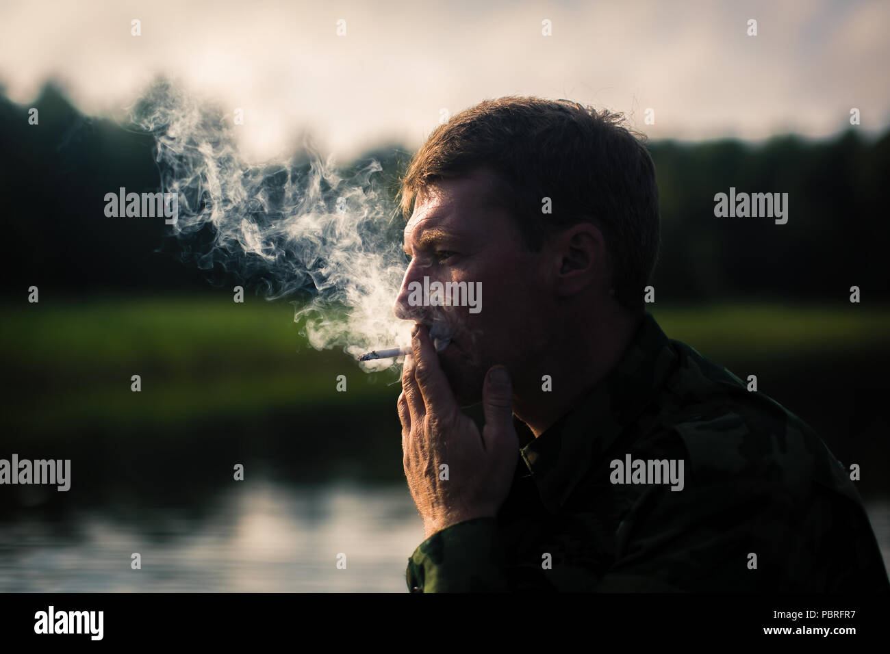 Man Smoking close-up, camouflage clothing, outdoor. Thick smoke and contour light. - Stock Image