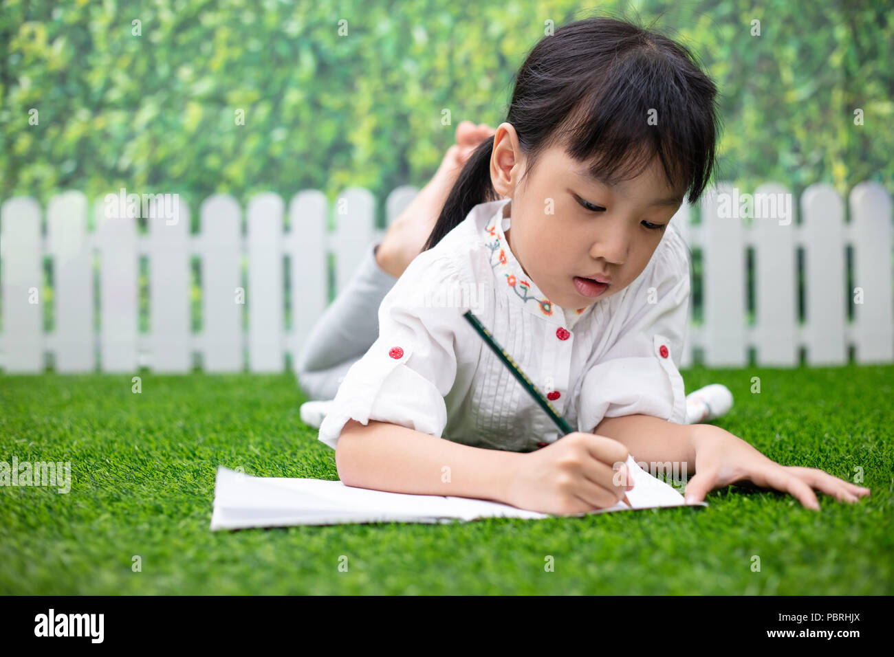 Asian Little Chinese girl kneeling on the grass and doing homework at outdoor park - Stock Image