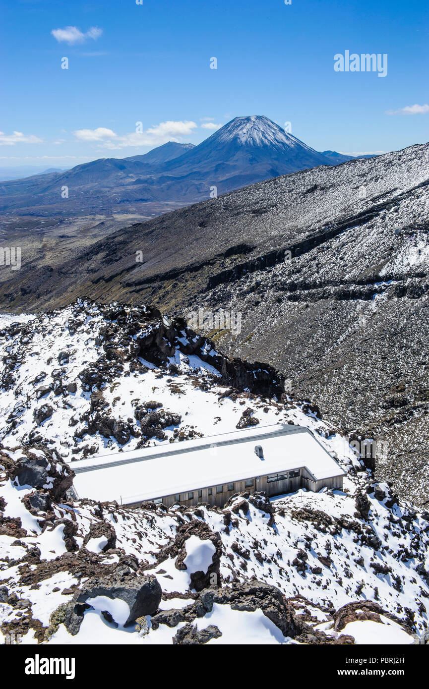 View from Mount Ruapehu on Mount Ngauruhoe with a ski cottage in the foreground, Unesco world heritage sight Tongariro National Stock Photo