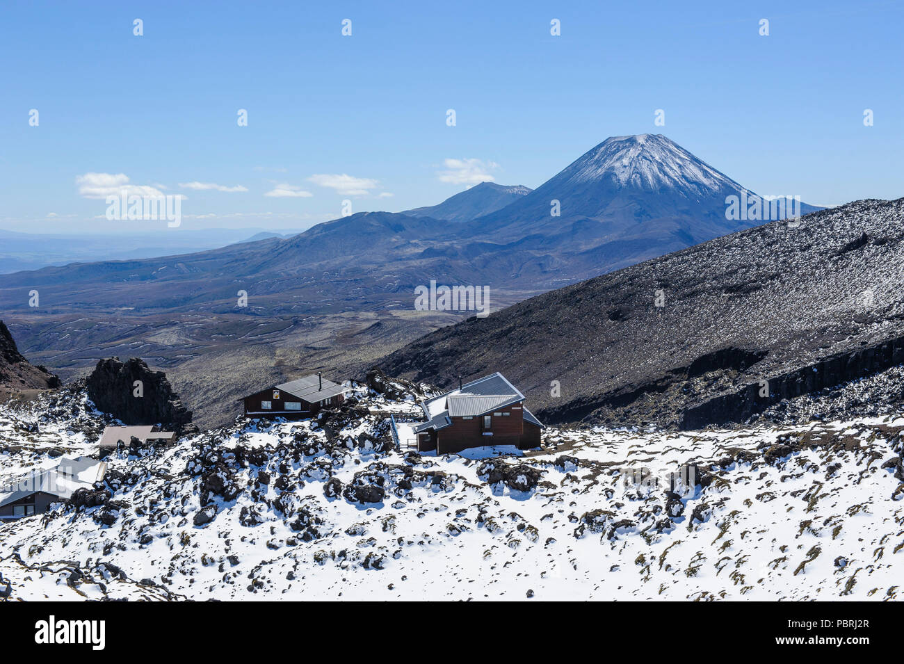 View from Mount Ruapehu on Mount Ngauruhoe with a ski cottage in the foreground. Unesco world heritage sight Tongariro National Stock Photo