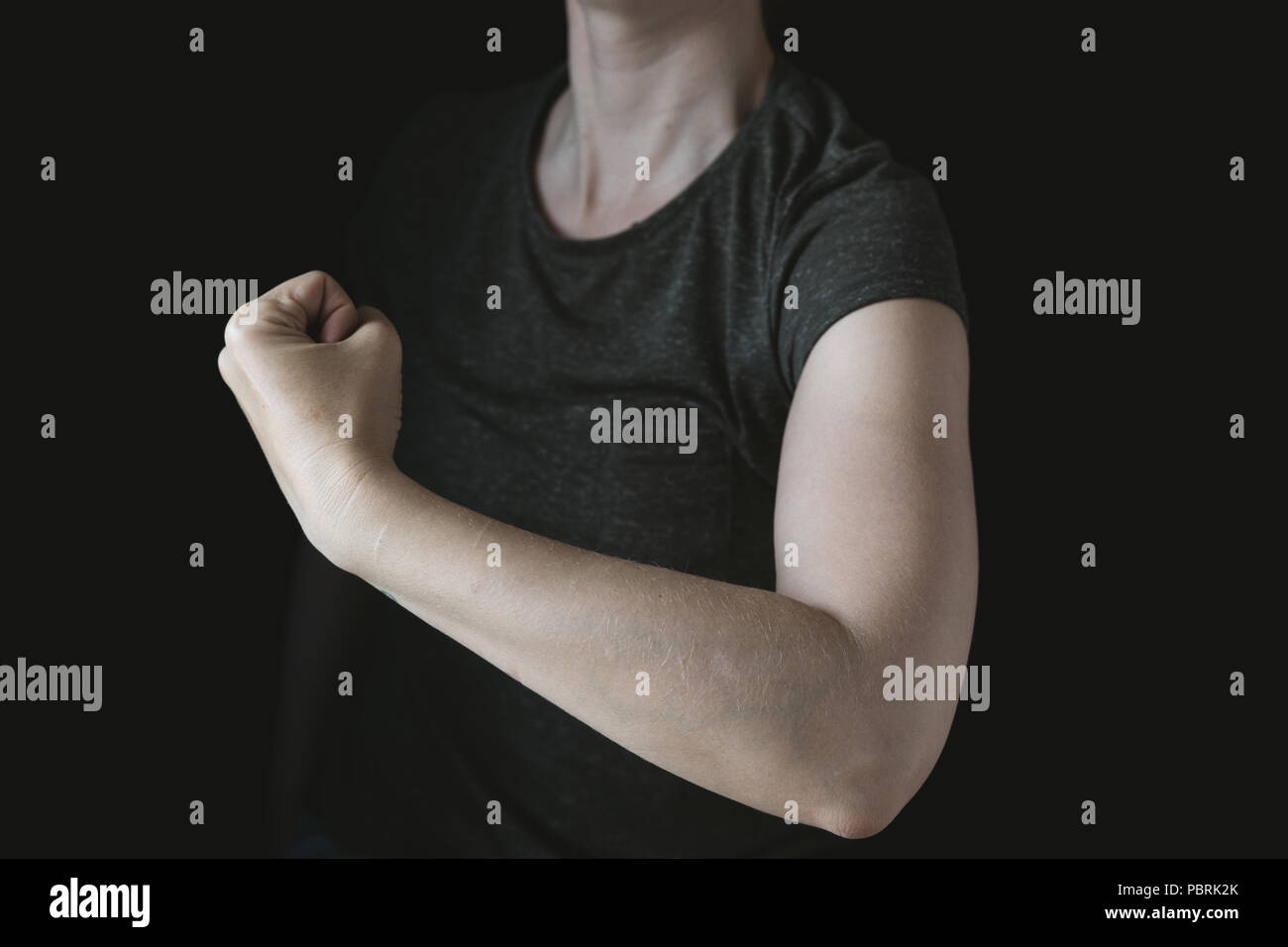 Symbolic picture, power woman, feminism, woman with tense arm muscles, black background, studio shot - Stock Image