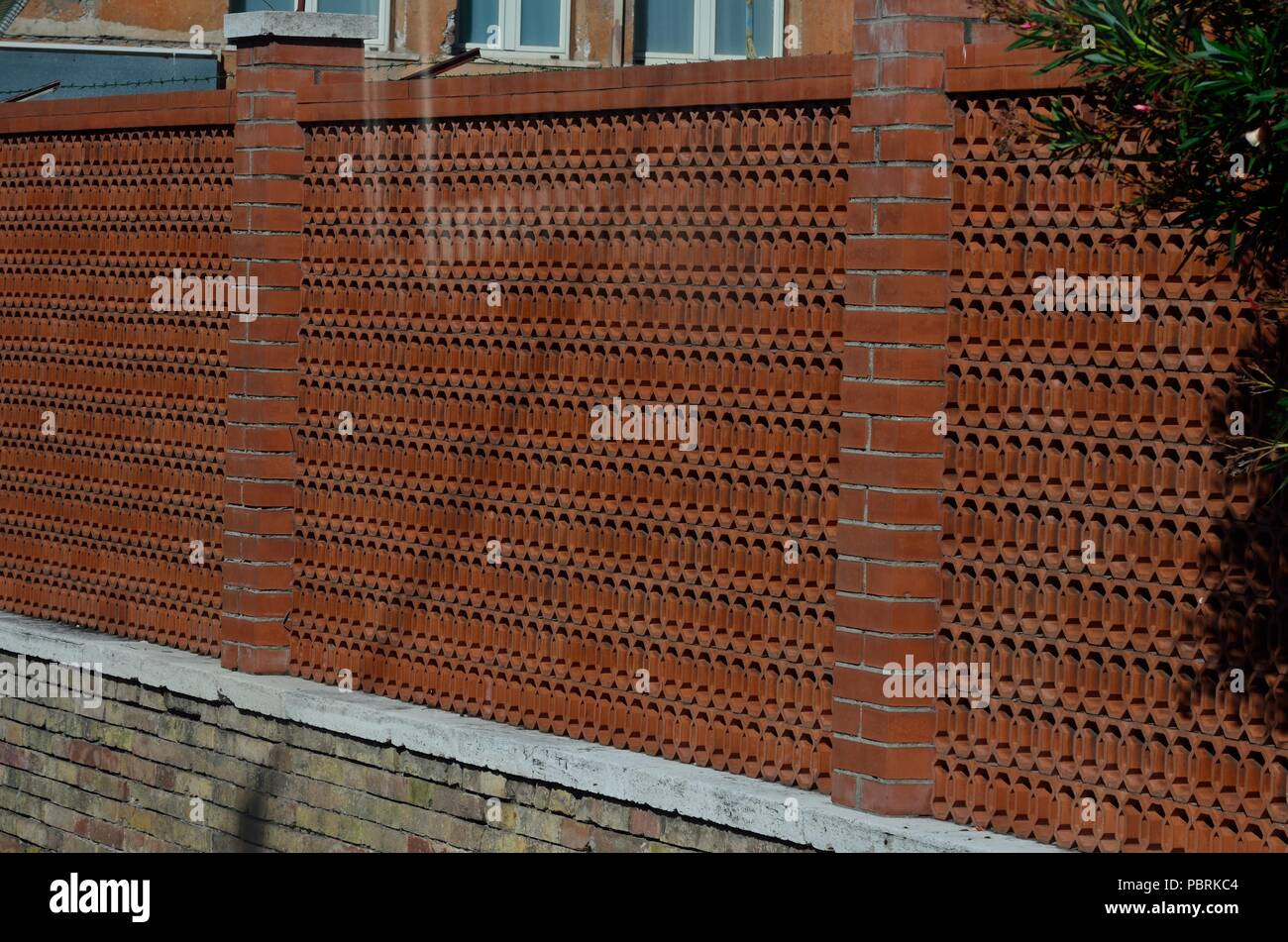 Red coloured compound wall made of terracotta tiles of a house rome