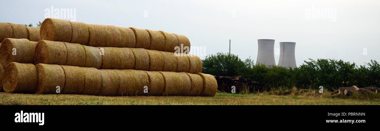 bale of straw and nuclear power station in background - Stock Image
