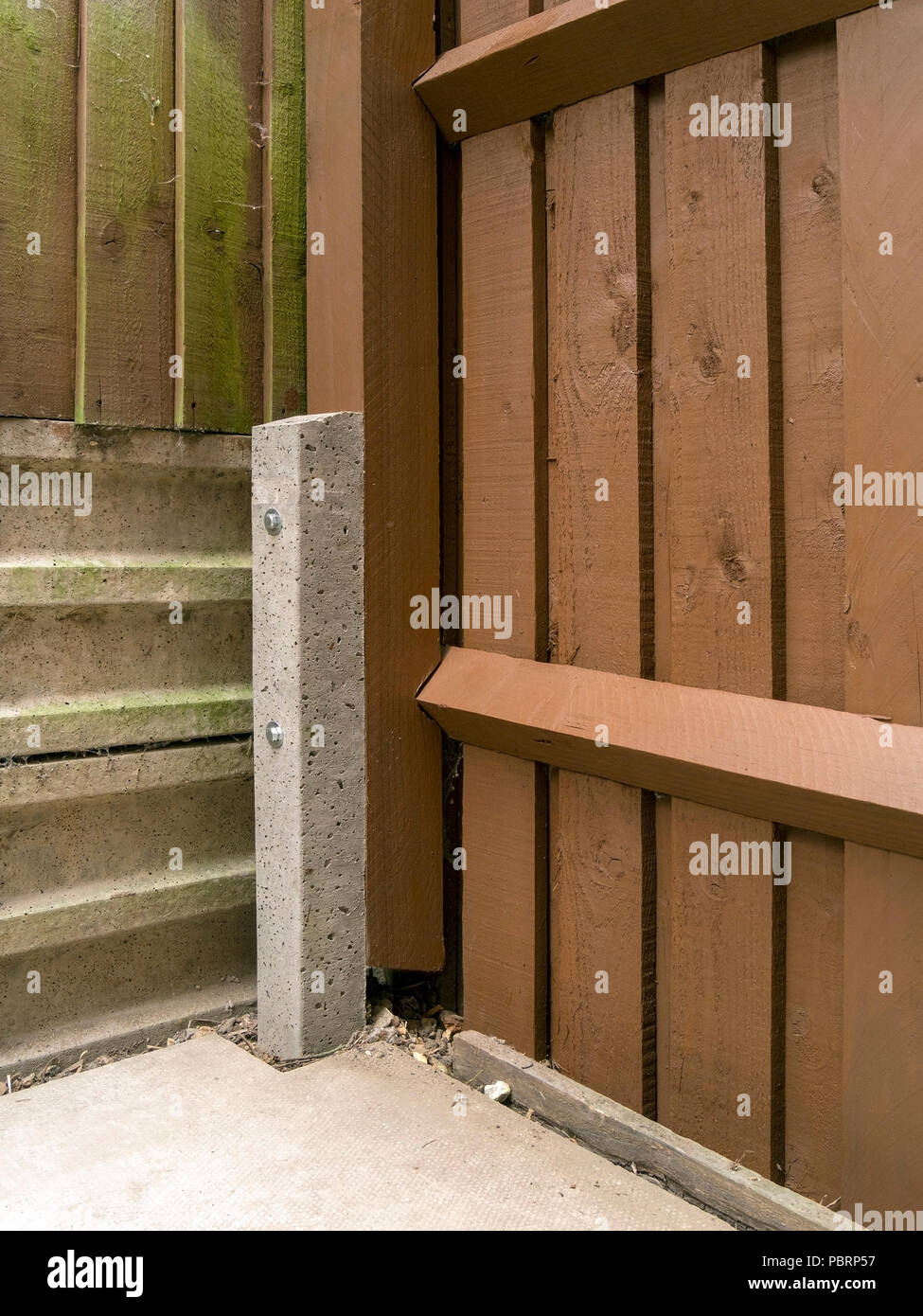 Reinforced concrete 'godfather' fence post spur used to repair wooden post and rail fence with pails - Stock Image