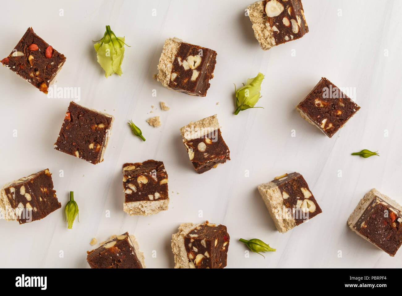 Raw vegan bars with nuts and cocoa, white background, top view. Healthy vegan food concept. - Stock Image