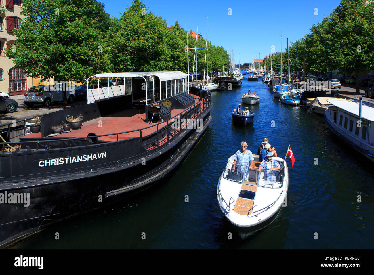 Small boats with tourists cruising along the canals in Christianshavn in Copenhagen, Denmark - Stock Image