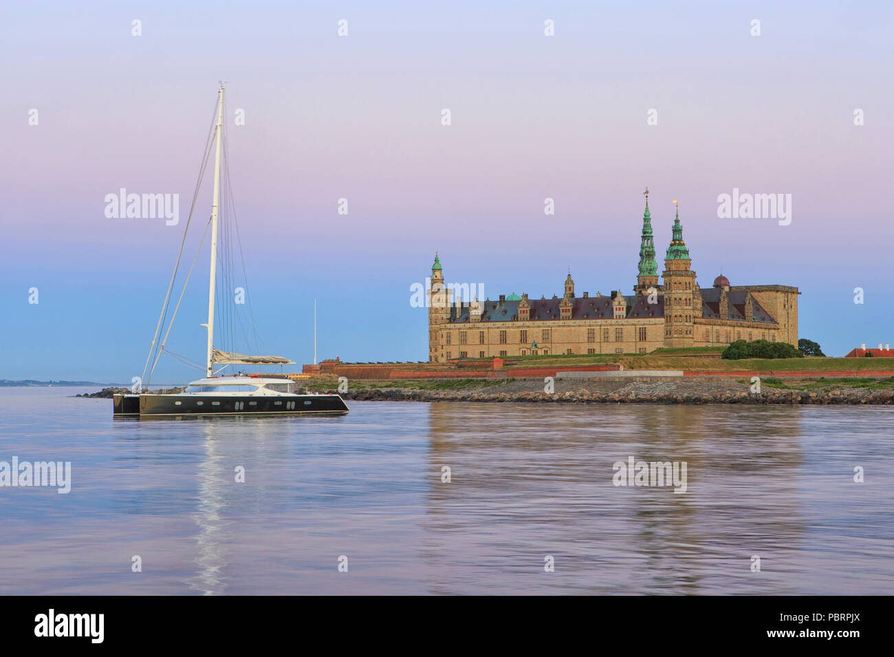 A catamaran for anchor at Kronborg Castle (a UNESCO World Heritage Site since 2000) at dusk in Helsingor, Denmark - Stock Image