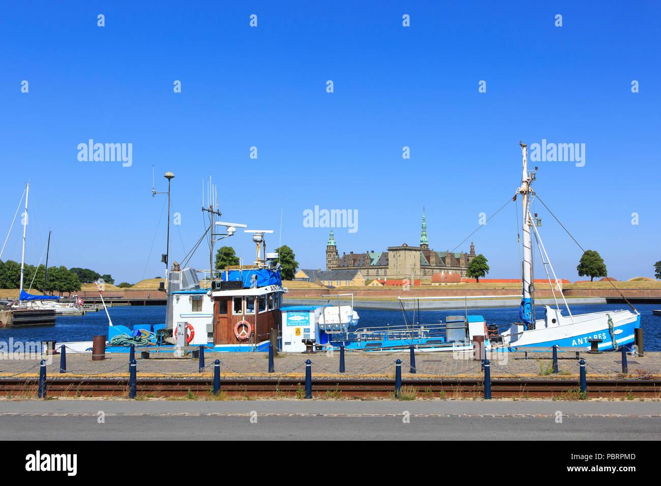 A fishing boat moored near Kronborg Castle (a UNESCO World Heritage Site since 2000) in Helsingor, Denmark - Stock Image