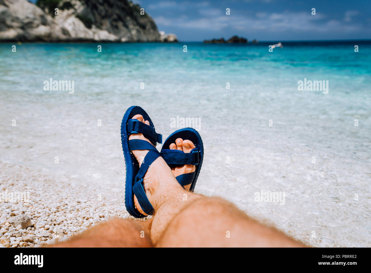 Young male crossed feets in blue flip-flop sandal sunbathing on sea beach - Stock Image
