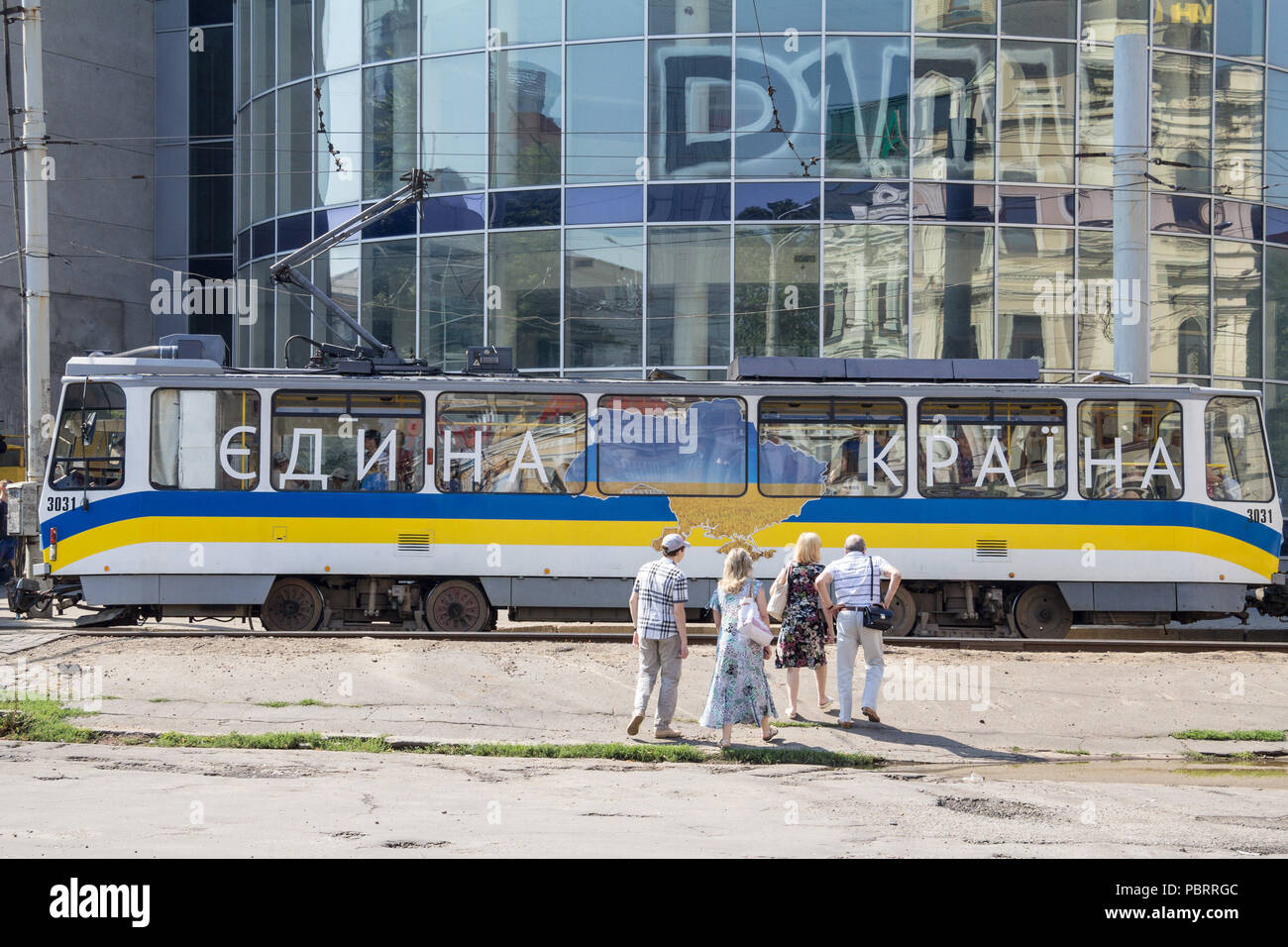 DNIPROPETROVSK, UKRAINE - AUGUST 15, 2018: Tram passing by the city center, with Ukrainian propaganda calling for unity with the slogan 'one country'  - Stock Image
