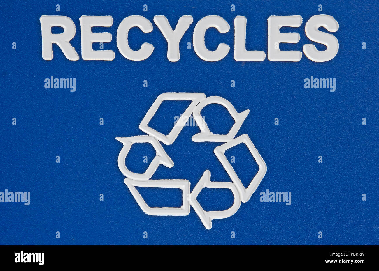 A large blue recylables container distributed by our city. Stamped on the lid is indicated all the variey of products that can be inserted and recyled - Stock Image