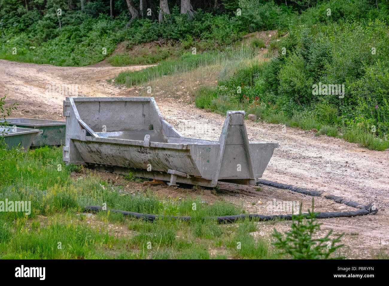 Dumpster on the edge of trail - Stock Image
