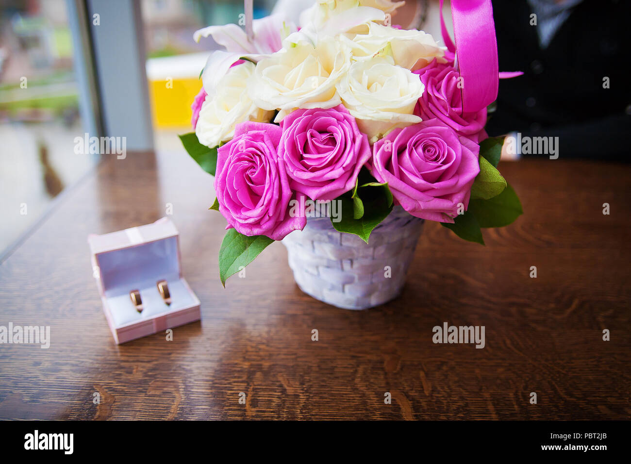 bouquet of beautiful and colorful flowers and wedding rings in a box - Stock Image