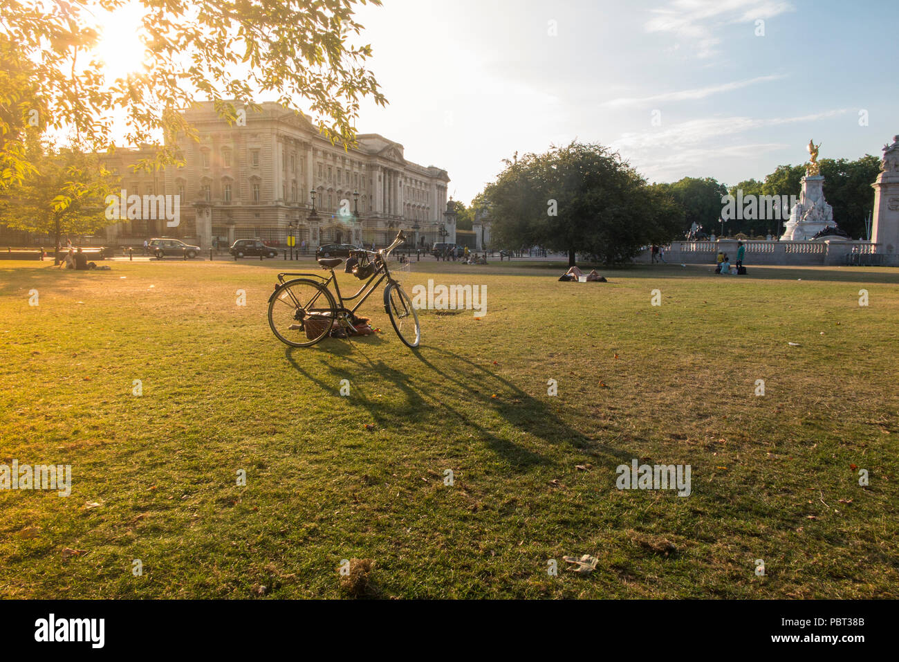 A lady snoozes by her bike outside Buckingham Palace on parched grass of a hot summer - Stock Image